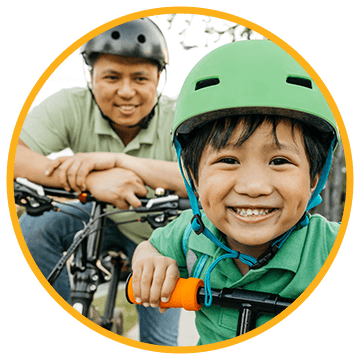 little boy with helmet on with his dad